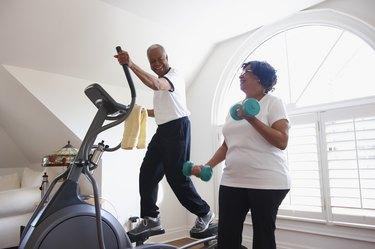 Smiling man using elliptical cardio machine at home with woman using hand weights