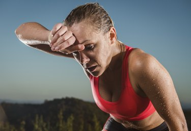 woman wiping sweat from forehead after body temperature increased during exercise