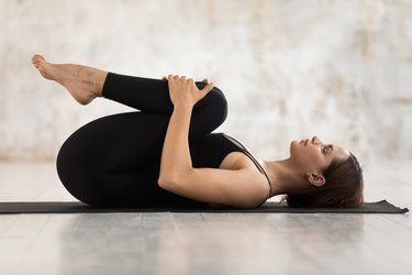 side view of a woman in wind relieving pose, as a natural remedy for upset stomach