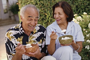 couple eating ice cream in bowls outside in moderation to manage blood pressure