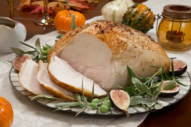 Mediterranean- style whole roasted tryptophan-rich turkey breast on a while platter surrounded by gourds