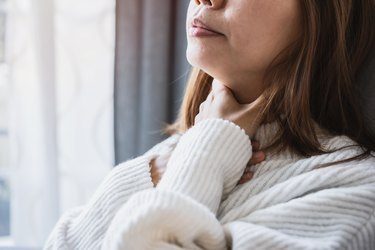 Close view of a woman with a sore throat after drinking