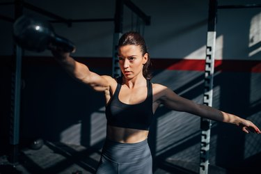 strong young caucasian woman doing a single-arm kettlebell swing as one of the best compound exercises for abs