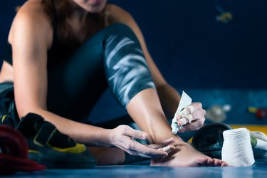 woman using pain relief cream on her ankle after exercise