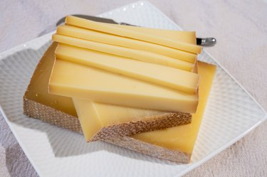 Sliced yellow cheese on a white plate is not a high-calorie food and does not have 1 calorie to avoid