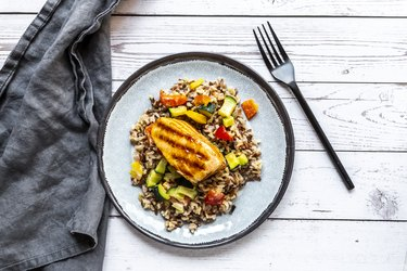 Top view of blue plate with roasted salmon, wild rice and vegetables that can ease hard belly fat symptoms