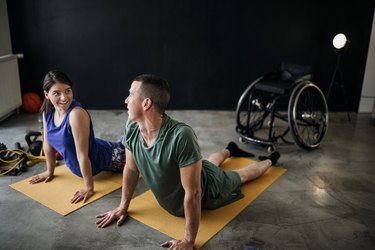 caucasian man and woman doing cobra yoga pose for flexibility, a type of fitness training, of with a wheelchair in the background