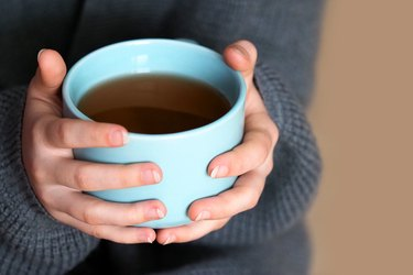Female hands holding a big cup of coffee, home comfort. Girl in oversize knitted sweater