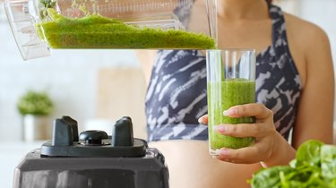 Sporty woman making healthy green fresh smoothie by blender for healthy drink, including vegetable and fruits