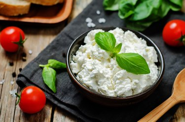 Tyrosine-rich ricotta cheese and basil in a bowl on a black napkin surrounded by cherry tomatoes and basil leaves.