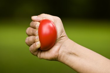closeup of a hand squeezing a red stress ball as one of the best thumb rehab exercises