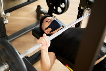 Asian man wearing an exercise face mask and doing a bench press