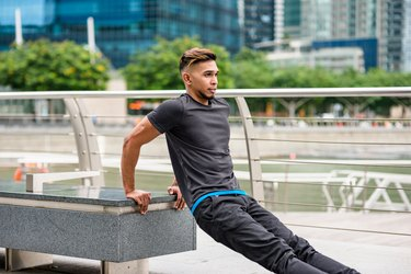 man doing triceps dips outdoors on a park bench