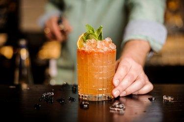 Bartender hand serving orange flavored vodka cocktail