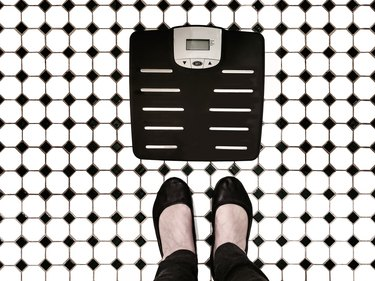 Body weight scales on tiled bathroom floor with woman's feet beside it like shes going to step on them - top view