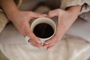 Top view of hands holding a mug of black coffee