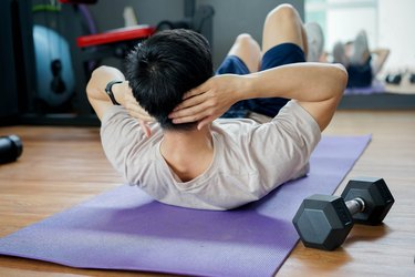 rear view of person doing single-dumbbell ab workout on purple yoga mat with weight
