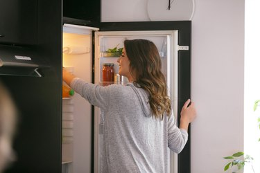 Happy woman taking food from the fridge