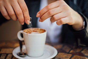 woman's hands pouring aspartame sugar packet into coffee