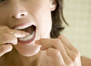 A woman in her 40s flossing her teeth