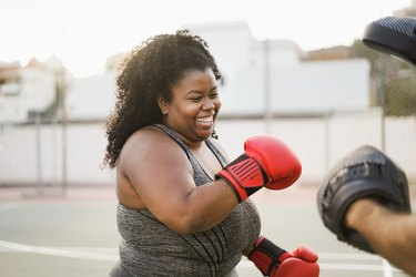 plus-sized black woman doing a boxing workout outside and smiling