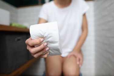 Woman's hand squeezes roll of toilet paper in toilet close-up