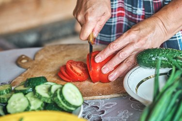 close up of hands cutting vegetables for meal prep