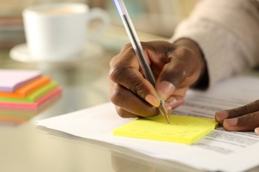 A person's hand writing on a sticky note on a desk