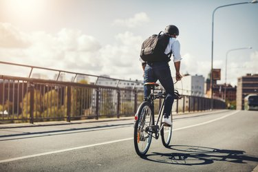 Rear view of man wearing backpack and helmet riding best bike for adults on bridge in city
