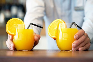 Waiter serving two glasses of orange juice for weight loss