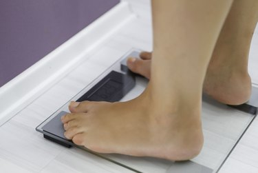 close up of person's feet on scale who is taking phentermine to lose weight
