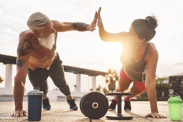 muscular man and woman doing push-ups together outside with dumbbells and protein shaker bottles at sunset.