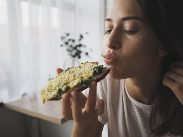 closeup of a young caucasian woman eating avocado toast before exercise