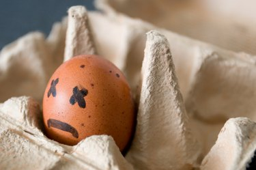An egg in a carton with a sad face drawn on it, to represent when burps smell like rotten eggs
