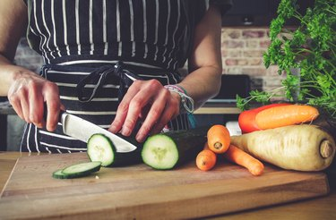 Person wearing striped apron cutting cucumber and carrots on a wooden cutting board in kitchen