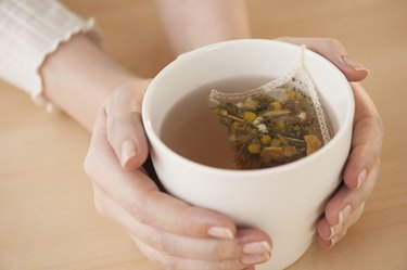 Woman holding cup with chamomile tea, as a hangover cure