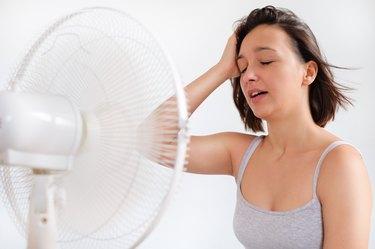 Woman feeling hot sitting in front of a cooling fan