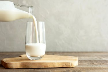 Pouring milk in a glass on a wooden board