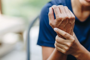 A woman holding her wrist because of arthritis pain
