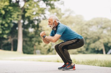 sideview of a fit senior man outside doing bodyweight squats, one of the best leg exercises for seniors