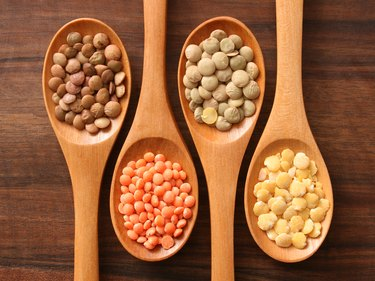 Different kinds of tyrosine-rich lentils in 4 small wooden spoons on a wooden cutting board.