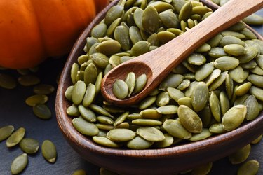 Tyrosine-rich pumpkin seeds in a wooden bowl and wooden spoon next to a pumpkin on a grey surface.