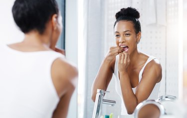 woman looking in the bathroom mirror and flossing her teeth to prevent morning breath