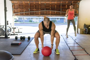 Couple doing cross-training HIIT workout in garage