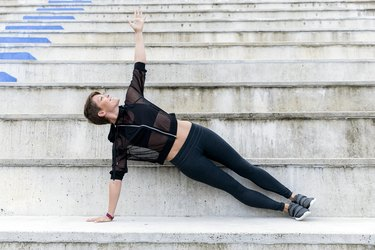 Athletic woman during workout on stairs, side plank