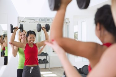 a woman having a hard time with an overhead press exercise, working with a female trainer