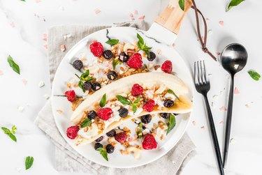 Breakfast banana split with berries on white plate