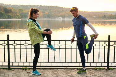 fit couple performing mobility exercises for runners by the water before their run