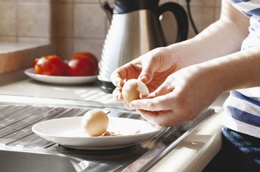 Hard-boiled eggs being shelled in kitchen