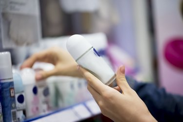 person's hands holding a stick of deodorant in the store